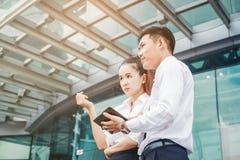 使用数字式片剂室外立场的亚洲企业夫妇会议 免版税库存照片
