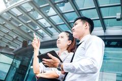 使用数字式片剂室外stan的亚洲企业夫妇会议 库存照片