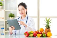 医治使用数字式片剂用果子和vegetab的营养师 免版税库存图片