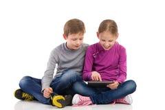 使用数字式片剂的两个孩子 免版税库存图片