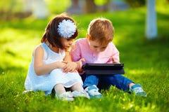 使用数字式片剂的两个逗人喜爱的孩子在夏天从事园艺 免版税库存照片