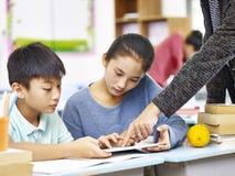 使用数字式片剂的亚裔基本的学童 免版税库存图片