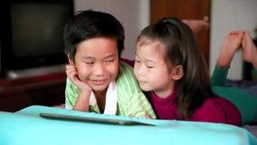 使用数字式片剂的亚裔孩子 了解银的计算机概念e关键膝上型计算机 影视素材