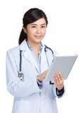 使用数字式片剂的亚裔医生 免版税库存照片
