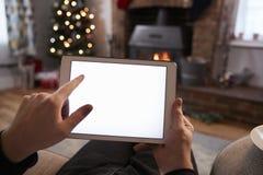 使用数字式片剂的人在装饰的屋子里为圣诞节 库存照片