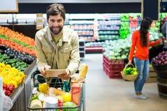 使用数字式片剂的人,当购物在超级市场时 免版税库存照片