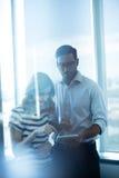 使用数字式片剂的企业夫妇反对玻璃窗 图库摄影