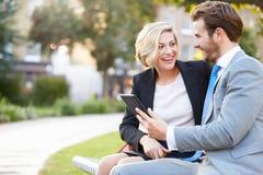使用数字式片剂的企业夫妇在公园长椅 免版税库存图片
