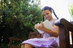 使用数字式片剂的低角度观点的微笑的女孩,当坐长木凳时 免版税库存照片