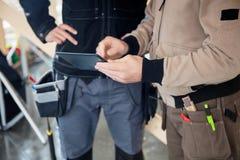 使用数字式片剂的体力工人在站点 免版税图库摄影