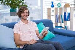 使用数字式片剂的公执行委员,当坐沙发在办公室时 库存照片