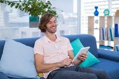 使用数字式片剂的公执行委员,当坐沙发时 库存照片