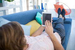 使用数字式片剂的公执行委员,当放松在沙发时 免版税图库摄影
