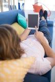 使用数字式片剂的公执行委员,当放松在沙发时 免版税库存照片