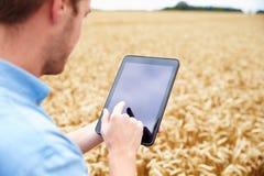 使用数字式片剂的农夫在麦田 免版税库存照片