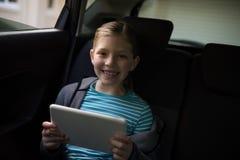 使用数字式片剂的十几岁的女孩在汽车后座  免版税库存照片