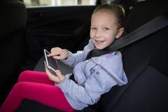 使用数字式片剂的十几岁的女孩在汽车后座  免版税库存图片