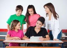 使用数字式片剂的十几岁的男孩和女孩在 免版税库存图片