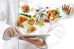 使用数字式片剂的厨师 库存照片