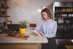 使用数字式片剂的可爱的年轻女服务员,当待命逆时 免版税库存图片