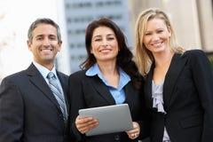 使用数字式片剂的商人和女实业家外面 库存图片