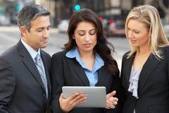使用数字式片剂的商人和女实业家外面 免版税库存照片