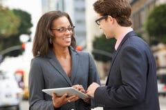 使用数字式片剂的商人和女实业家外面 免版税库存图片