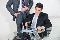 使用数字式片剂的商人在一次会议与 免版税库存图片