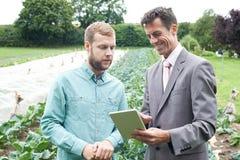 使用数字式片剂的商人在与农夫的会谈期间F的 免版税库存图片