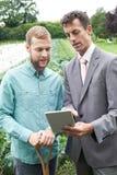 使用数字式片剂的商人在与农夫的会谈期间F的 免版税库存照片