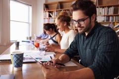 使用数字式片剂的商人在书桌在繁忙的办公室 免版税库存图片