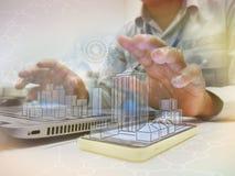 使用数字式片剂的商人有图画设计大厦的 图库摄影