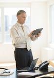 使用数字式片剂的商人,当支持书桌时 库存图片