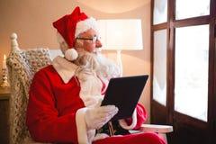 使用数字式片剂的圣诞老人在客厅在圣诞节时间 免版税库存图片