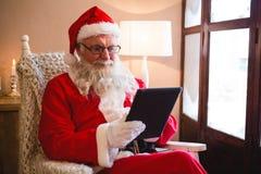使用数字式片剂的圣诞老人在客厅 库存图片