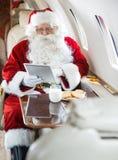 使用数字式片剂的圣诞老人在私人喷气式飞机 免版税库存照片