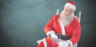 使用数字式片剂的圣诞老人的综合图象 库存照片