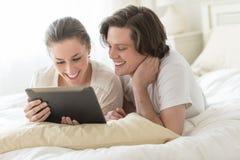 使用数字式片剂的夫妇在床上 免版税图库摄影