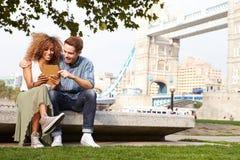使用数字式片剂的夫妇有塔桥梁的在背景中 库存图片