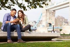 使用数字式片剂的夫妇有塔桥梁的在背景中 免版税库存图片
