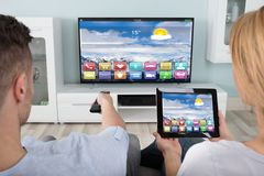使用数字式片剂的夫妇观看的电视 免版税库存照片