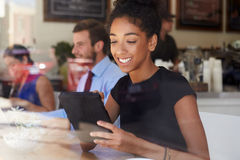 使用数字式片剂的女实业家在咖啡店 免版税库存照片