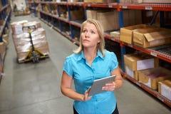 使用数字式片剂的女实业家在配给物仓库 免版税库存照片