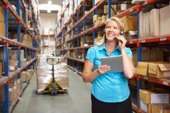 使用数字式片剂的女实业家在配给物仓库 免版税图库摄影