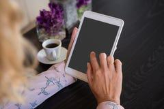 使用数字式片剂的女实业家由咖啡杯在咖啡馆 免版税库存照片