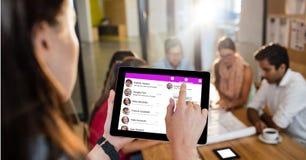 使用数字式片剂的女实业家社会网站有同事的谈论在背景 库存图片