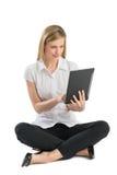 使用数字式片剂的女实业家,当坐地板时 库存图片