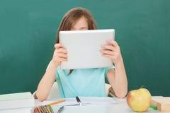 使用数字式片剂的女小学生反对黑板 免版税图库摄影
