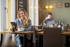 使用数字式片剂的孕妇在Coffeeshop 免版税图库摄影