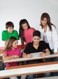 使用数字式片剂的学生在书桌 免版税库存图片